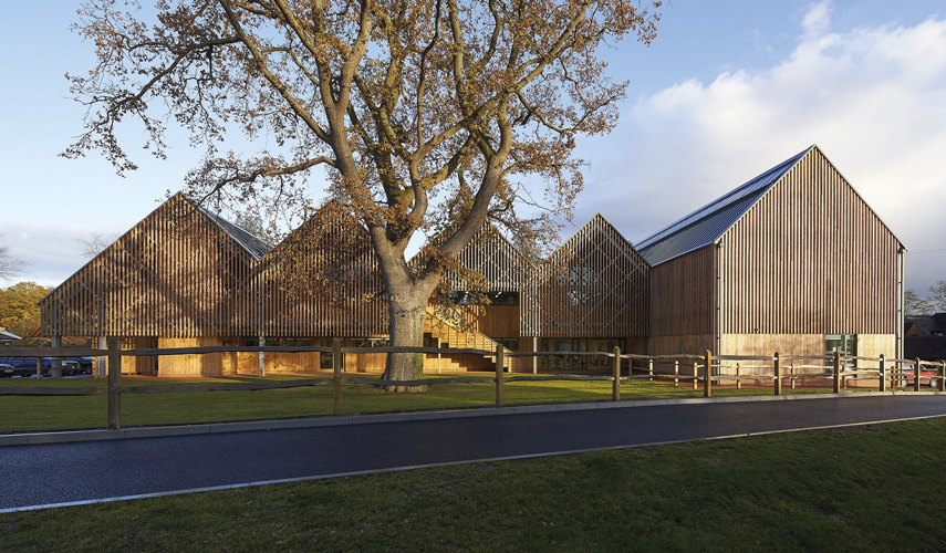 <p>The L-shaped building form creates a new green with an ancient oak tree at its centre. <span>© Hufton+Crow</span></p>
