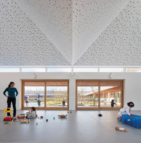 <p>The inclined ceilings of the nursery classrooms are expressed externally by pitched roofs clad with cedar shingles. © Alan Williams </p>