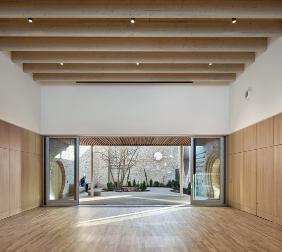 <p>The large multi-purpose room in the community centre opens on to a walled garden. © Alan Williams </p>