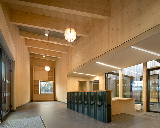 <p>Spruce glulam beams and CLT act as a warm and textured backdrop to the new school entrance. © Anthony Coleman</p>