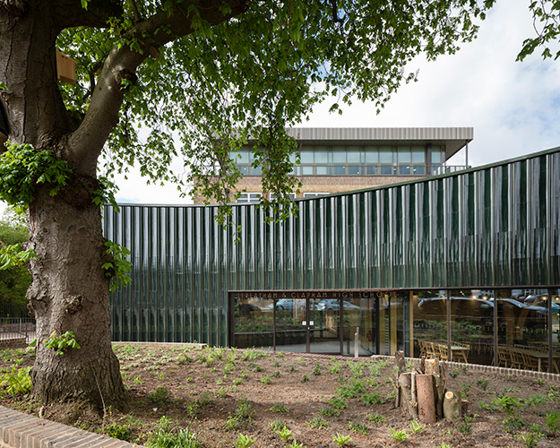<p><span>The curved wall of the new school entrance is clad with a lustrous terracotta rainscreen. © Anthony Coleman</span></p>