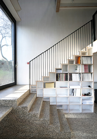 <p>Open plywood bookcases support the staircase. Photography: © Adam Currie</p>
