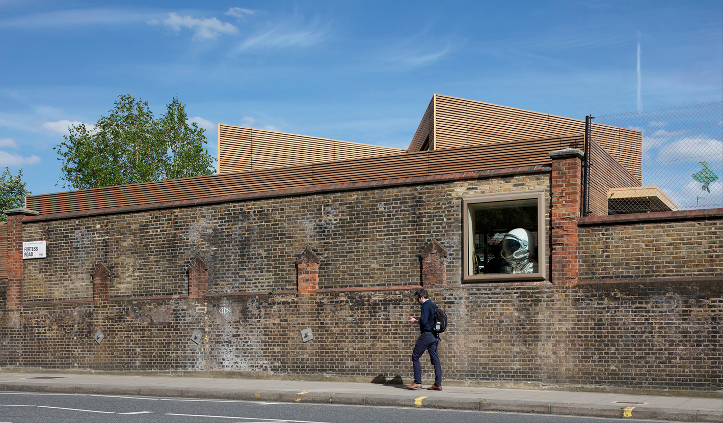 <p>The Victorian boundary wall is punctured by a single large window which gives glimpses of the activities inside. Photography: © Nick Kane</p>