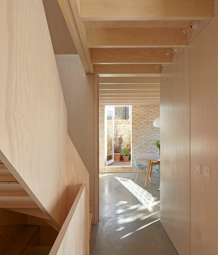<p>The plywood wall panels extend to the undersides of the Douglas fir joists. Photography: © Edmund Sumner</p>