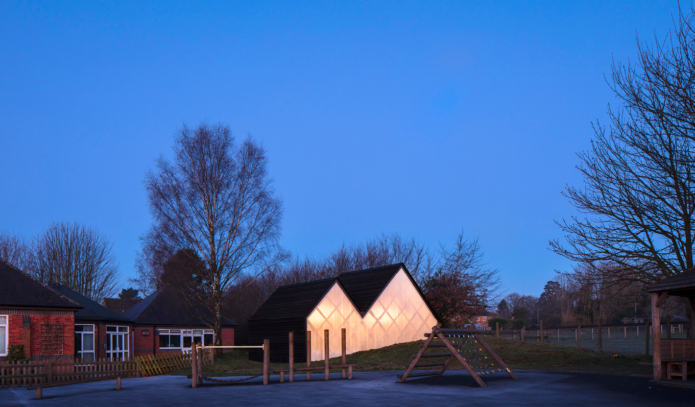 <p>At night the timber structure can be seen through the polycarbonate-glazed gables. Photography © Will Scott</p>