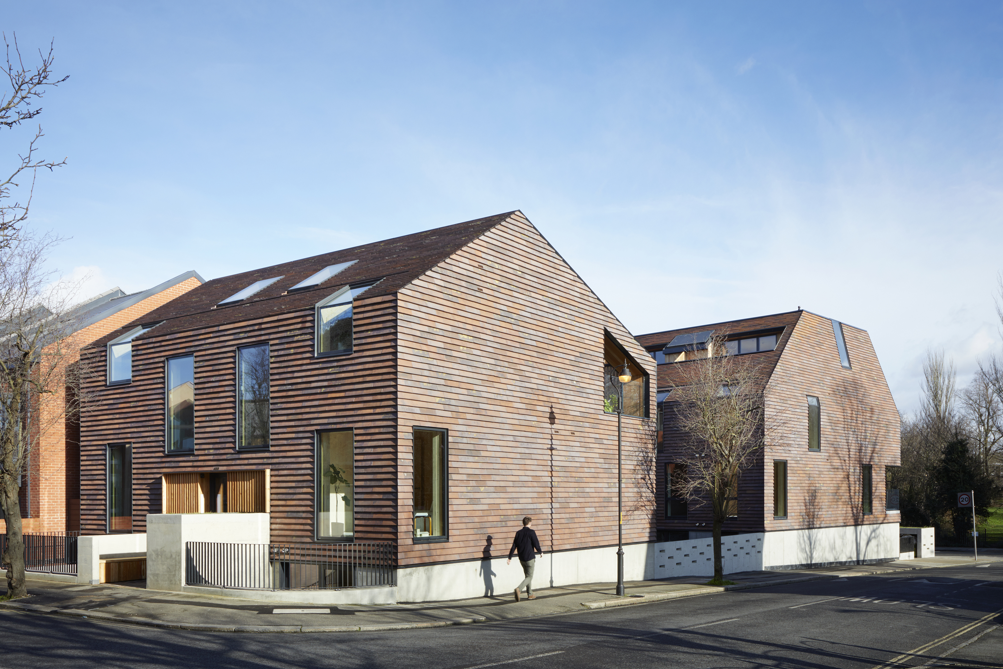 <p>Both apartment blocks are clad with red clay shingles. © Jack Hobhouse</p>