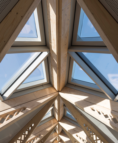 <p>Pairs of LVL trusses rise to the ridge of the mezzanine and support triangular glazed roof lights.</p> <p><span>© Nigel Young/Foster + Partners</span></p>