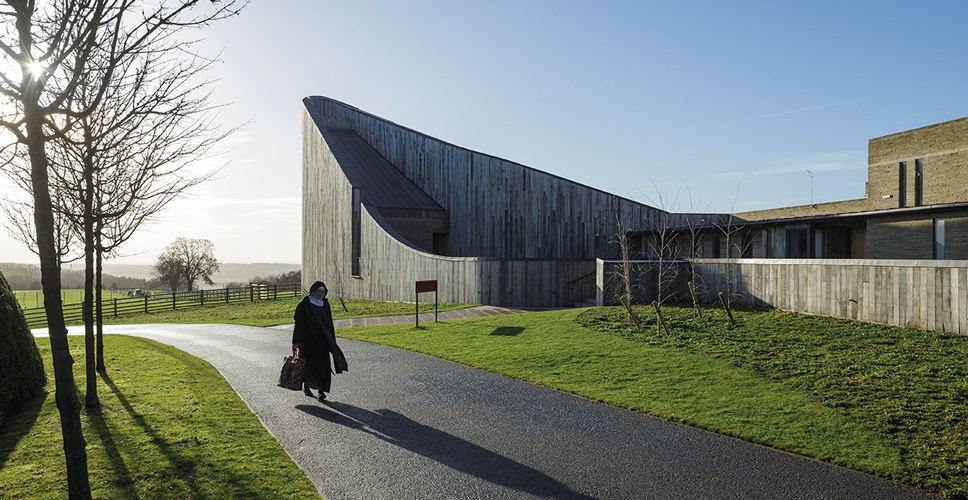 <p>The church and chapel walls curve and rise, clad with a rainscreen of vertical oak boards.</p> <p><span>© Peter Cook, Tim Crocker</span></p>