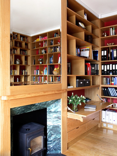<p>The library is lined with European oak veneered shelves which frame the fireplace.</p> <p><span>© Fisher Hart/VIEW</span></p>