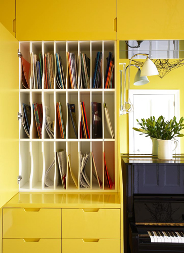 <p>The music room is fitted with MDF cupboards painted bright yellow to contrast with the black piano.</p> <p><span>© Fisher Hart/VIEW</span></p>