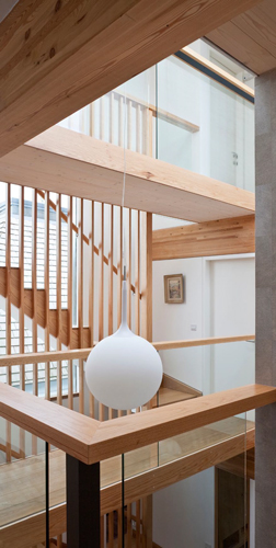 <p><span>The light-filled triple-height hall has a timber staircase which rises to first and second floors, with walkways connecting bedrooms.</span></p> <p><span>© David Butler</span></p>