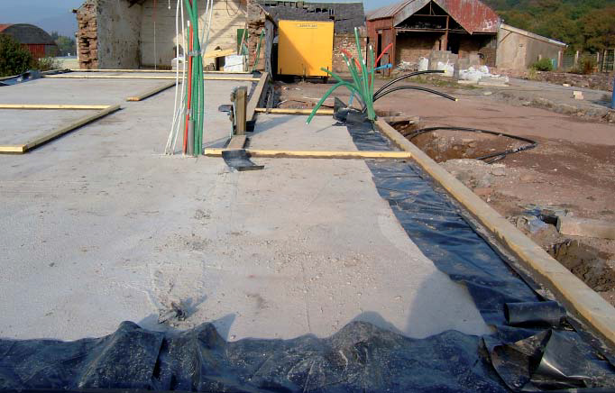 <p>Concrete floor slab with DPC turned over the top. Old Victorian buildings in the background.</p> <p>© Steve Mackan</p>