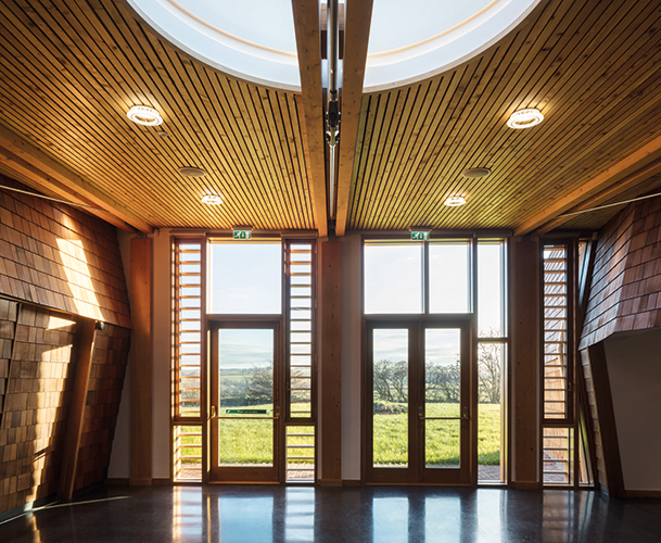 <p>The timber-lined reception space; glulam beams and columns, a boarded larch ceiling, walls of cedar shingles and oak-framed glazing. © Simon Kennedy Photography</p>
