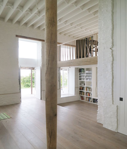 <p>The ceiling joists in the drawing room are exposed and supported by oak beams and a tapered oak column. <span>© Johan Dehlin</span></p>